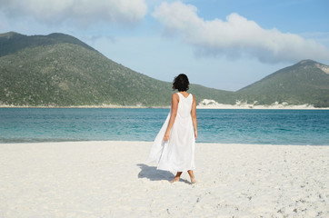 Back view of woman in white at the beach looking at the sea