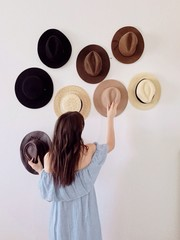 Woman placing hats on wall