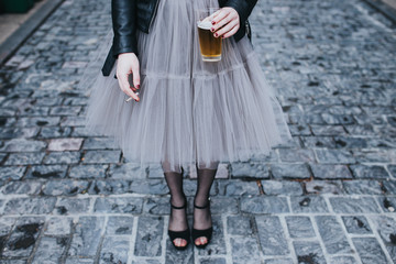 Fashionable woman standing on street with glass of beer and cigarette