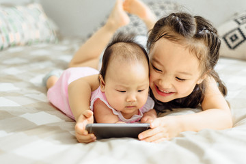 Cute littler girl and her baby sister at home