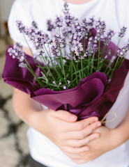A child holding a gift of a Lavender plant.