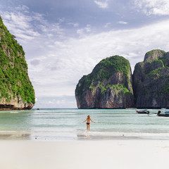 Back view of unrecognizable woman walking in water at Phi-Phi island