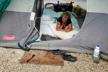 A woman who  is a former combat veteran takes a moment to collect herself after it began to rain inside her tent and and she realized her things were getting wet outside her heavily damaged house after Hurricane Irma in Cudjoe Key, Florida
