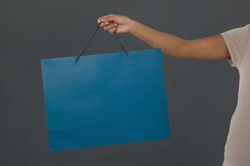 Cropped image of woman holding blue shopping bag