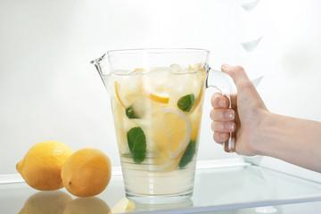 Female hand taking jug of lemonade from fridge