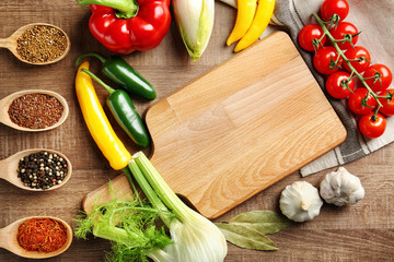 Wooden board and vegetables with spices on kitchen table. Cooking classes concept