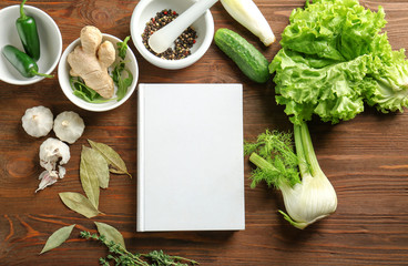 Notebook and vegetables on kitchen table. Cooking classes concept