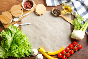 Parchment paper with vegetables and spices on kitchen table. Cooking classes concept