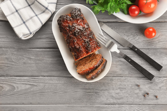 Plate with tasty baked turkey meatloaf on wooden table