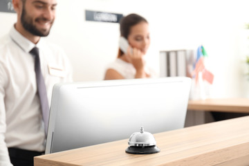 Service bell and two busy receptionists in hotel