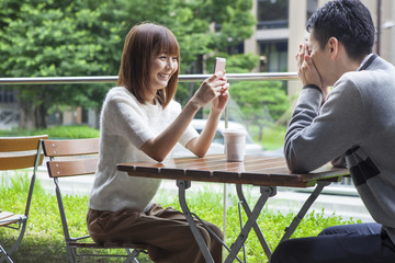 A woman trying to take a picture of a lover in a cafe terrace with a smartphone