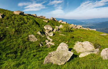 huge boulders on a grassy slope in mountains. lovely mountain landscape with sky full of beautiful clouds