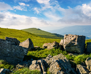 huge boulders on a grassy hillside at sunrise. gorgeous mountain landscape with beautiful sky