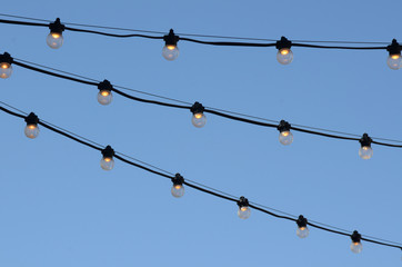 strings of illuminated electric light bulbs outdoors against blue sky