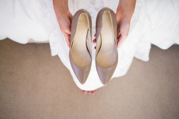 Low section of bride holding shoes while sitting in fitting room