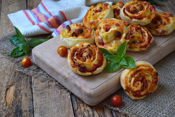 Buns of yeast dough with tomatoes, ham and cheese on a wooden background. Mini pizzas. homemade baking