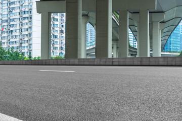 Empty road surface floor with city overpass viaduct bridge in shanghai.
