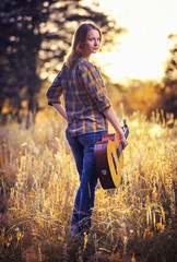 Image from the back of a attractive young woman on the plaid shirt  with a acoustic guitar on a  yellow autumn meadow in backlit sunset light.