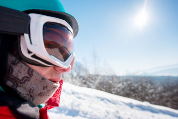 Close up cropped profile shot of a male snowboarded wearing helmet and skiing mask on a beautiful sunny winter day at ski resort copyspace lifestyle active sports people equipment concept