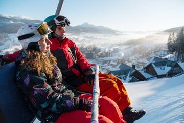 Close-up of couple man and woman snowboarders on a cable ski lift in the morning in Bukovel enjoying a beautiful view of the Carpathian Mountains copyspace recreation active sport seasonal concept