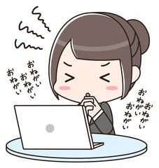 パソコンの前で祈る女性