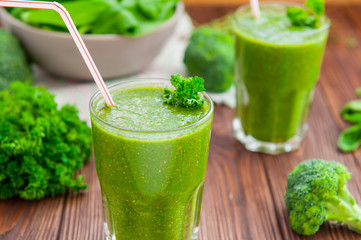 Fresh green smoothies in glass with ingredients on the dark rustic wooden table. Healthy, diet, detox lifestyle concept. Selective focus. Copy space.