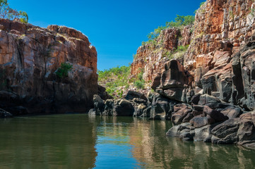 Rocky cliff face with reflections on the Katherine River banks, the end point of the cruise tour in the dry season at Katherine Gorge in Nitmiluk National Park, Northern Territory, Australia.