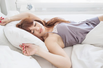 A beautiful girl is sleeping in a white bed, a bright bedroom. Good morning. Attractive woman. A gray nightgown. American