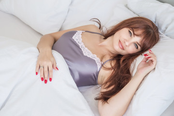 Beautiful young woman lies in white bed. Good morning. Smile. Attractive European-looking girl. American. Gray nightgown