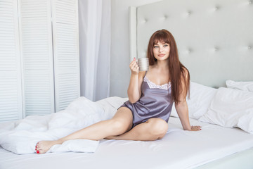 Beautiful caucasian girl sitting in bed with a mug of morning coffee, cocoa, tea. White bed and interior. Gray pajamas, nightgown. American.