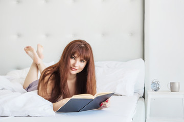 Beautiful woman is lying in bed with a black book. White bed and interior. Gray pajamas. Good morning