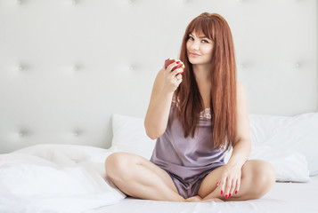 Beautiful woman sits in a lotus position on a bed with a red chamomile. White interior. Gray pajamas. Good morning
