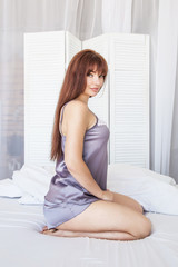 Beautiful woman sitting on a bed in silk gray pajamas. White interior. Good morning