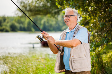 Happy senior man is fishing on sunny day.