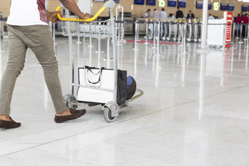 Airport luggage Trolley with suitcases, unidentified man woman walking in the airport, station, France