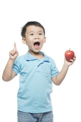 Asian baby boy holding and eating red apple, isolated on white