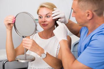Doctor is examining woman patient behind mirror before the procedure