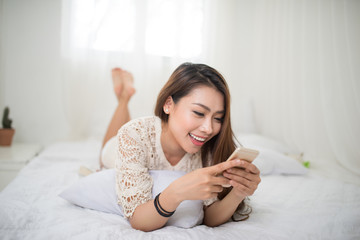 Woman Relaxing in bed and listening to music, relaxing in her living room
