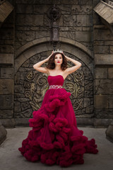 A beautiful woman, a queen in a red luxurious dress, stands on the background of a medieval, Gothic emblem with an arch and holds a silver caron with crystals. The Princess at the Castle