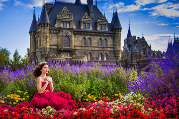 A beautiful woman, a princess in a red dress, sits by in a blooming garden. An ancient castle in the background. Medieval fantasy, European palace
