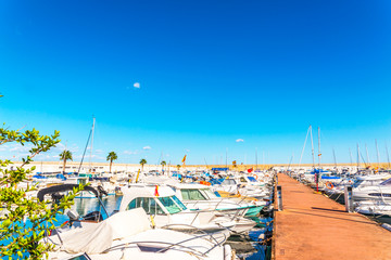 Beautiful luxury yachts and motor boats anchored in the harbor, hot summer day and blue water in the marina, blue sky