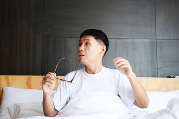 Asian man is lazy to wake up in the morning at bed room.