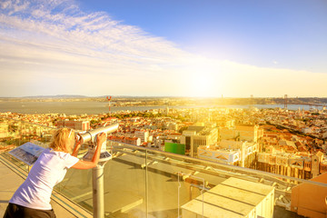 Woman traveler looking skyline of Lisbon, Portugal, with binocular binocular from Amoreiras 360 panoramic terrace. Aerial view of 25 April Bridge, Cristo Rei and Tagus River at sunset.