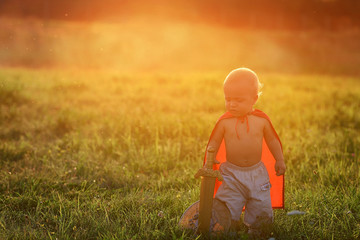 Little boy king outdoors at sunset with ray of light