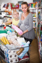 Mother and girl choosing goods in chemistry rows