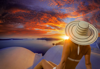 Woman with hat watching Oia village on santorini island in Greece