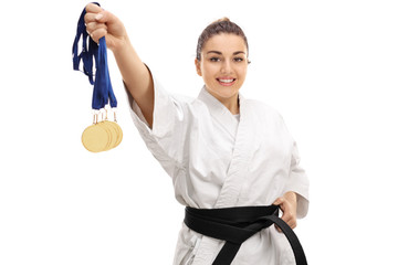 Karate girl showing gold medals and smiling