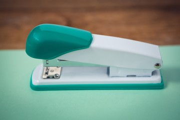 Close up of stapler on turquoise paper