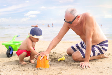 Little boy and grandfather playing at the beach