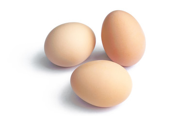 Three fresh brown hen eggs, isolated on white background